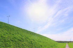 Sun in blue sky, bright green lawn, walkway and road on hill Stock Images