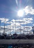Sun, blue sky, heavy white stratus clouds, sailboats docked. The sun in a cloudy blue sky over sail boats in a boat yard with many masts pointing to the sun stock image