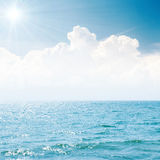 Sun in blue sky over clouds and sea Royalty Free Stock Images