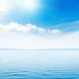Sun in blue sky over sea Stock Photography