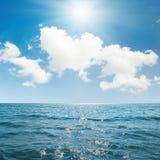 Sun in blue sky over sea Stock Image