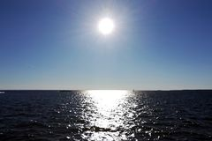 The Sun in the blue sky and the sun glare on the water. Sun on a blue sky and sun glare on the water stock photo
