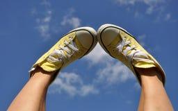 Sun a brûlé les pieds de la femme dans des espadrilles jaunes lumineuses sur le fond profond de ciel bleu Photographie stock libre de droits