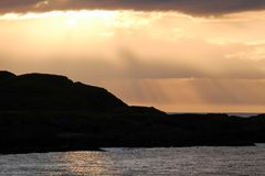 Sun breaking through the clouds. Evening sunlight over offshore rocks, Islay - Scotland Stock Photos