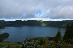 Sun Breaking Through the Clouds to a Blue Lake in the Azores. Sun shining through the gray clouds to Sete Cidades royalty free stock photo
