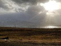 The Sun and Ghostly Moutnains. The sun breaking through dark clouds clouds on an Iceland morning, with the mountains in the distant having an otherwise ghostly stock photos