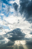 The sun breaking through  dark storm clouds with sky background Stock Photo