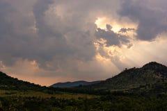 Sun breaking through storm clouds over African savannah royalty free stock photos