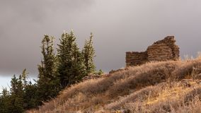 The sun breaks through low clouds and fog to light an old stone ruin a grassy hillside and some ice rimmed pines on Brain Head. Peak in Southern Utah royalty free stock photography