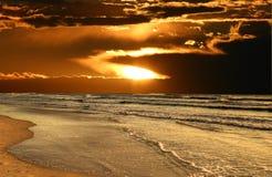 Sun Breaks Through Over Beach. Waves roll in at dawn as the sun breaks through clouds stock photos