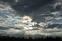 Sun-Brechen warf Wolken Stockfotos
