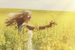 Sun brilha através do cabelo louro do ` s da mulher quando girar no campo da violação fotografia de stock