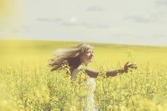Sun brilha através do woman& x27; cabelo louro de s quando girar no campo da violação imagem de stock royalty free