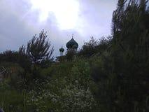 Sun brilha entre as nuvens acima da igreja imagem de stock