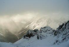 Sun brilha no vale na opinião alemão dos cumes de um monte nevado para baixo na névoa fotos de stock royalty free