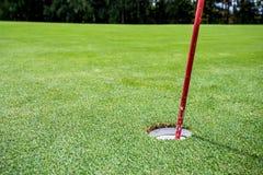 Sun brilla detrás de una bandera del golf Imágenes de archivo libres de regalías