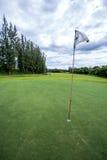 Sun brilla detrás de una bandera del golf Foto de archivo libre de regalías