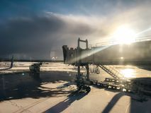 Sun brilla detrás del puente del jet en el aeropuerto fotografía de archivo