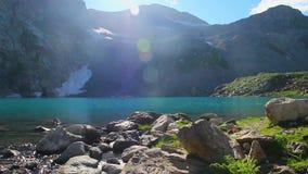 Sun brilla sobre el pico de montaña, paisaje azul impresionante del lago almacen de video