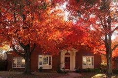 Sun brillant par le rouge brillant laisse ombrager une belle maison traditionnelle de brique avec haut tout prêt de décorations d photos libres de droits