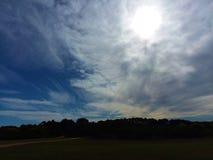 Sun brillant par les nuages whispery au-dessus des marécages photos stock