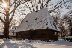 Sun brille au-dessus d'une ferme en bois traditionnelle couverte par neige Photo stock