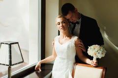 Sun brille par une fenêtre sur une belle jeune mariée tandis que prairie de marié Photos libres de droits