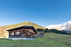 Sun burned timber chalet hut on austrian mountains Stock Photos