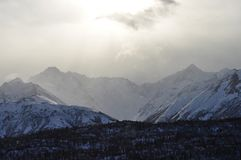 Haze Clears Over the Mountains. The sun burns through clearing haze over snowy mountain peaks in Alaska Stock Images
