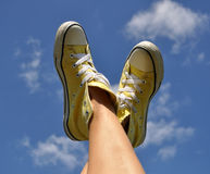 Sun burnt woman's feet in bright yellow sneakers against the deep blue sky background Royalty Free Stock Photos