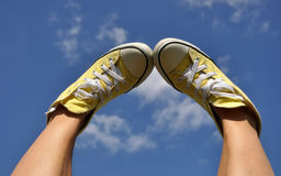 Sun burnt woman's feet in bright yellow sneakers against the deep blue sky background Royalty Free Stock Photography