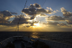Sun burst over sea from ships bow Stock Image