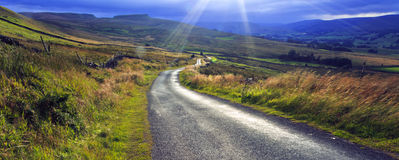 Sun bursting through cloud above Crag Side Road Yorkshire Dales Stock Images