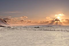 The sun bursts from behind a cloud over the frozen landscape of stock photos