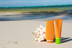 Sun care and cockshell. Summer protection cosmetics on a sand Stock Photo