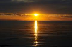 The Sun cayó abajo de las nubes en el tiempo de la puesta del sol Fotografía de archivo