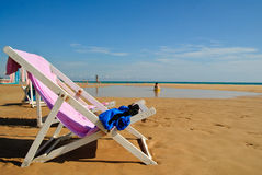 Sun chair on beach in paradise. Sun chair on a beach in paradise. People are playing and running in the background, it�s evening and sun is low on the horizon Stock Photography
