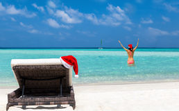Sun chair with christmas hat and girl in bikini on a tropical beach royalty free stock images