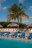 Sun chairs next to the pool in a tropical resort Royalty Free Stock Photos