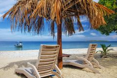 Sun chairs with thatched umbrella on a white sandy beach. South Sea Island, Mamanuca group, Fiji royalty free stock images