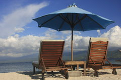 Sun chairs and umbrella on a beach Royalty Free Stock Photos