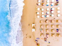 Sun chairs and umbrellas bird`s eye view on sand beach in Greece. Greek Island Lefkada in the Mediterranean Sea is a well known tourist destination for the Stock Photography
