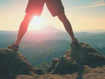 Sun chaud entre les jambes nues Les jambes minces en pantalon et sandales font l'étape sur la roche dans la jungle Photo libre de droits