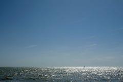 Sun che glinting fuori dalla superficie dell'oceano Fotografia Stock