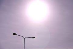 Sun che irradia giù su un palo della luce Immagine Stock