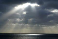 Sun che lucida attraverso le nubi sopra la costa sud Fotografia Stock