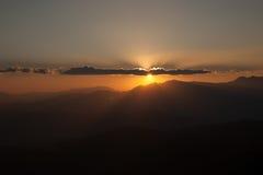 Sun che mette dietro le nuvole e le montagne Fotografie Stock Libere da Diritti