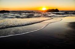 Sun che mette dietro un Seastack sulla costa dell'Oregon fotografia stock
