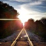 Sun che mette facendo uso dei binari ferroviari fotografia stock