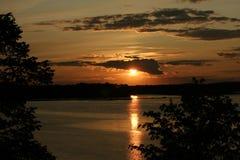 Sun che mette sopra il lago Immagine Stock